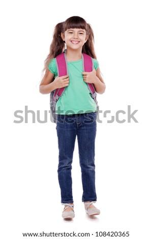 Full length portrait of a schoolgirl standing on white background - stock photo