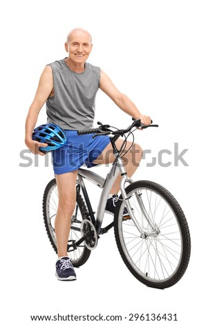 Full length portrait of a senior biker holding a blue helmet seated on his bike and looking at the camera isolated on white background - stock photo