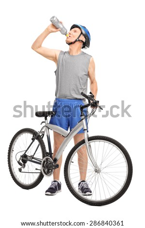 Full length portrait of a senior biker standing behind his bicycle and drinking water isolated on white background - stock photo