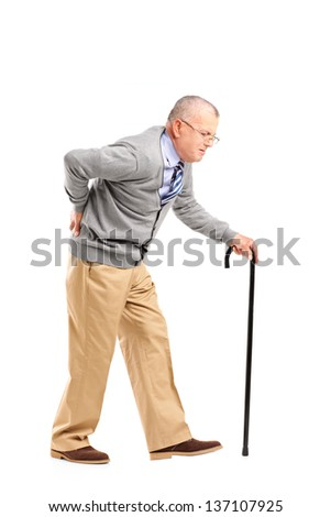 Full length portrait of a senior gentleman walking with cane and suffering from back pain isolated on white background