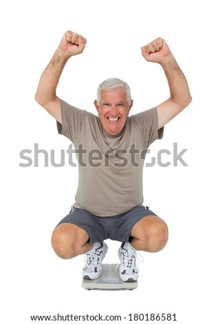 Full length portrait of a senior man cheering on weight scale over white background - stock photo