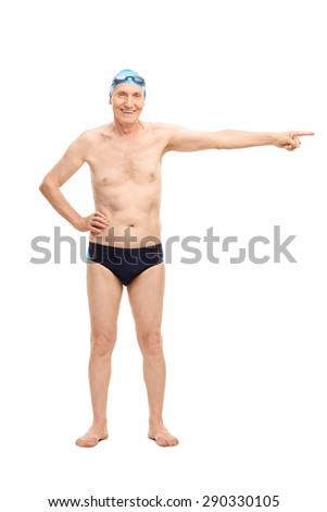 Full length portrait of a senior man in black swim trunks pointing with his hand towards right and looking at the camera isolated on white background - stock photo