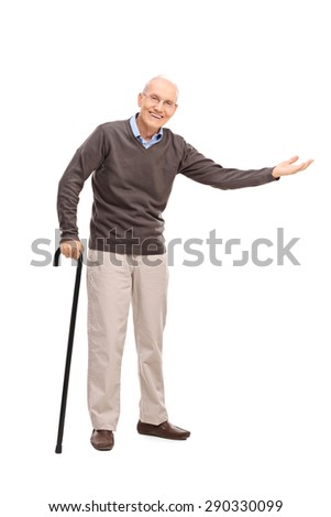Full length portrait of a senior with a cane smiling and gesturing with his hand isolated on white background - stock photo