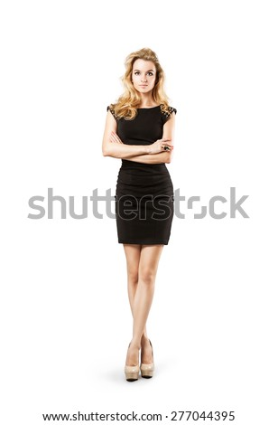 Full Length Portrait of a Sexy Blonde Woman in Little Black Fashion Dress. Crossed Arms and Legs. Closed Body Posture. Body Language Concept. Isolated on White. - stock photo