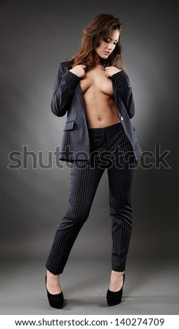 Full length portrait of a sexy businesswoman posing on gray background