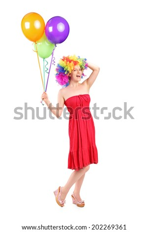 Full length portrait of a silly woman with wig holding balloons isolated on white background - stock photo