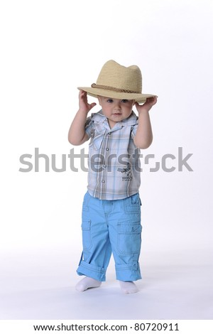 Full length portrait of a small boy wearing a straw hat