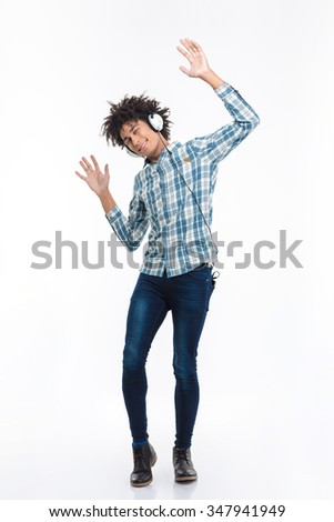 Full length portrait of a smiling afro american man listening  music in headphones and dancing isolated on a white background - stock photo