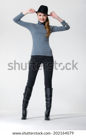 full-length portrait of a smiling blond woman in a studio - stock photo