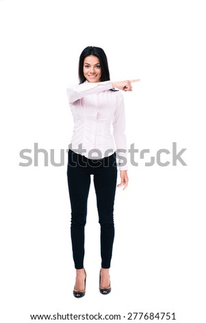 Full length portrait of a smiling businesswoman pointing finger away isolated on a white background. Looking at camera - stock photo