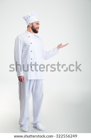 Full length portrait of a smiling chef cook showing copyspace on the palm and looking away isolated on a white background - stock photo