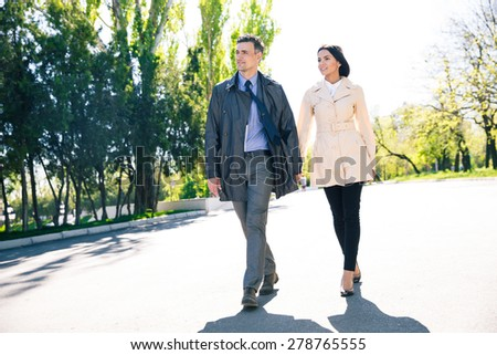 Full length portrait of a smiling couple walking outdoors - stock photo