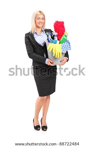 Full length portrait of a smiling female holding a bucket full with cleaning supplies isolated on white background - stock photo