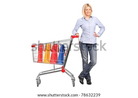 Full length portrait of a smiling female posing next to a shopping cart full with shopping bags isolated on white background - stock photo