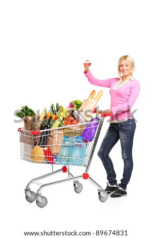 Full length portrait of a smiling female showing a credit card and pushing a shopping cart isolated on white background - stock photo