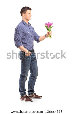Full length portrait of a smiling guy holding flowers isolated on white background - stock photo