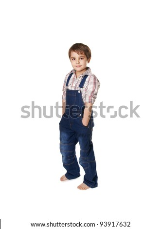 Full length portrait of a smiling happy little boy standing with hands in pockets on white background
