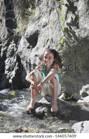 Full length portrait of a smiling little girl sitting on rock by stream - stock photo