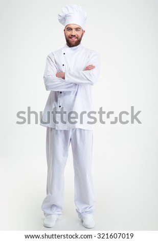 Full length portrait of a smiling male chef cook standing with arms folded isolated on a white background