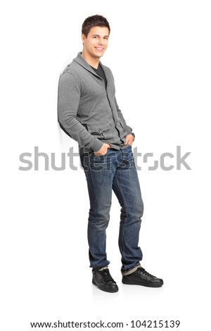 Full length portrait of a smiling male leaning against wall isolated on white background - stock photo