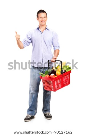 Full length portrait of a smiling man holding a shopping basket and giving thumb up isolated on white background