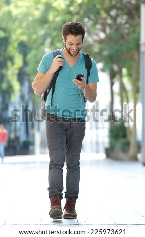 Full length portrait of a smiling man walking in the city with mobile phone and bag - stock photo