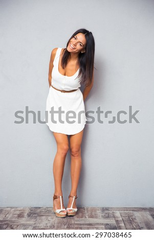 Full length portrait of a smiling pretty woman in trendy white dress posing on gray background - stock photo