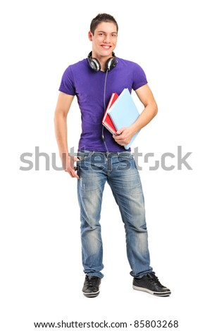 Full length portrait of a smiling school boy with headphones holding books isolated on white background - stock photo