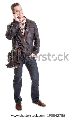 Full length portrait of a smiling student carrying a bag and talking on a phone isolated on white background - stock photo