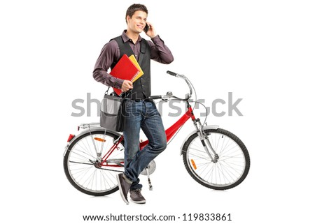 Full length portrait of a smiling student holding books and talking on a phone next to a bike isolated on white background - stock photo