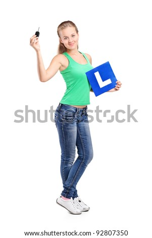 Full length portrait of a smiling teenager holding a L plate and car key isolated on white background - stock photo