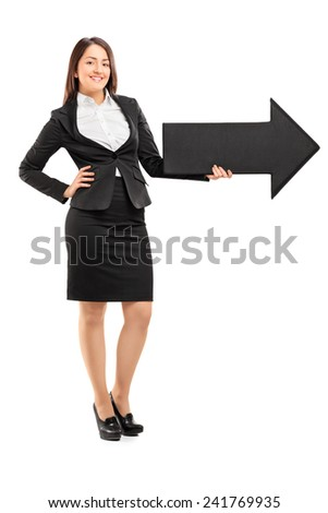 Full length portrait of a smiling woman holding a big black arrow pointing right isolated against white background - stock photo