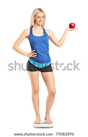 Full length portrait of a smiling woman holding a red apple and standing on a weight scale isolated on white background - stock photo