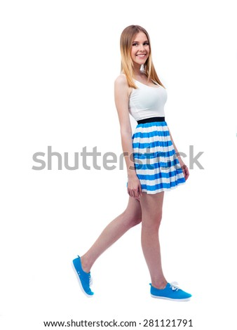 Full length portrait of a smiling woman in dress walking over white background. Looking at camera - stock photo