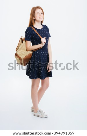 Full length portrait of a smiling woman standing with backpack isolated on a white background - stock photo
