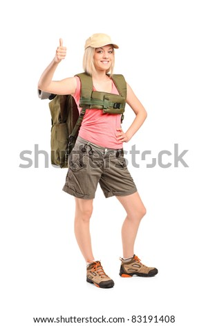 Full length portrait of a smiling woman with backpack givimh thumb up isolated on white background