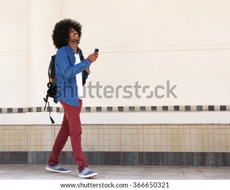 Full length portrait of a smiling young black man walking with bag and mobile phone - stock photo