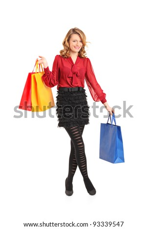Full length portrait of a smiling young female posing with shopping bags isolated on white background - stock photo
