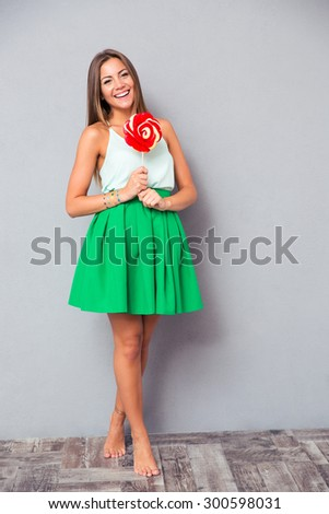Full length portrait of a smiling young girl standing with lollipop on gray background - stock photo