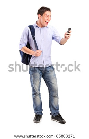 Full length portrait of a smiling young man looking at a cell phone isolated on white background - stock photo