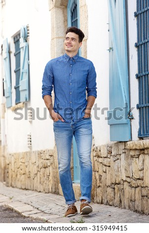 Full length portrait of a smiling young man walking in town - stock photo