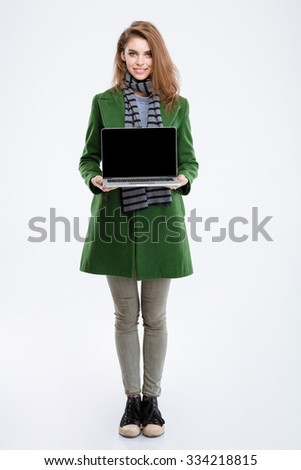 Full length portrait of a smiling young woman in green coat showing blank laptop computer screen isolated on a white background - stock photo