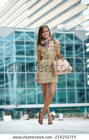 Full length portrait of a smiling young woman posing in the city with handbag