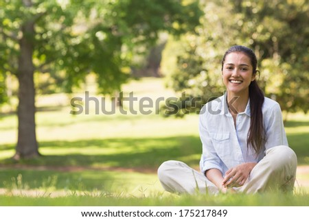 Full length portrait of a smiling young woman sitting on grass in the park