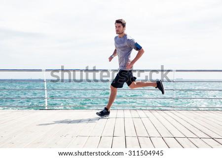Full length portrait of a sports man running outdoors near sea - stock photo