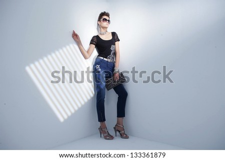 full-length portrait of a styled professional model wearing modern sunglasses holding purse �light background