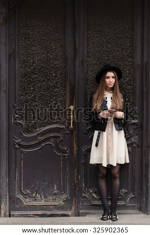 Full length portrait of a stylish hipster girl dressed in classy clothes holding cell telephone while standing near big vintage door, young beautiful female with trendy look chatting on mobile phone - stock photo