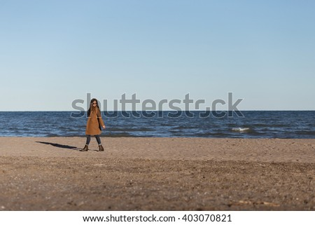 Full length portrait of a stylish young brunette on a sunny afternoon by the lake. She's walking along the lakeshore, wearing coat, sweater, jeans, sunglasses; looking down. Copyspace - stock photo