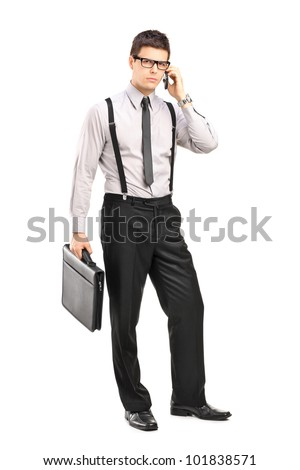 Full length portrait of a stylish young man holding a breifcase and  talking on a mobile phone isolated on white background