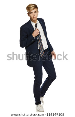 Full length portrait of a stylish young man in suit holding his tie, over white background - stock photo